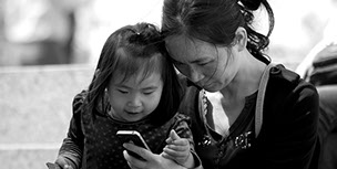 Chinese grandmother and her granddaughter playing with an iPhone